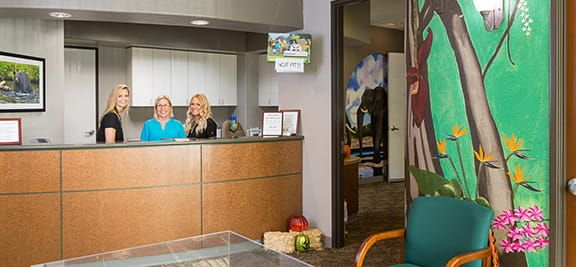 Office staff standing behind the receptionist desk with a jungle painted on the wall